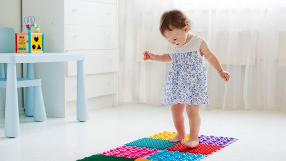 A child walking on a play mat.